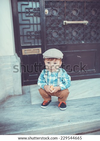 seating cute little stylish boy in classic style in the city in cap - stock photo