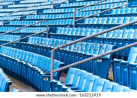 Seating rows in a stadium with weathered chairs - stock photo
