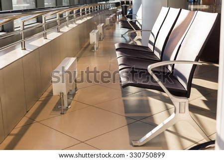 seats in front of the window in the waiting room at the airport