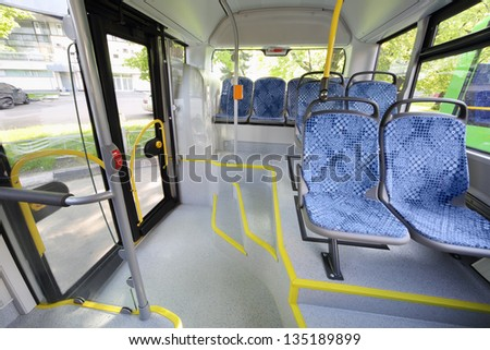 Seats in passenger compartment of empty city bus with big windows.
