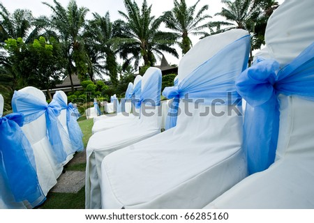 Seats with blue sashes at an outdoor garden wedding ceremony - stock photo