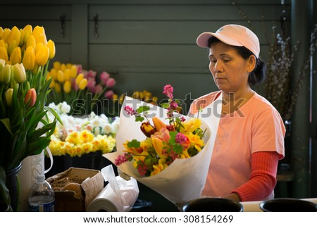 SEATTLE- APR 11, 2014: A flower vendor at Pike Place Market arranges a bouquet. The famous public market is known as a great source of fresh blooms which are grown on nearby flower farms. - stock photo