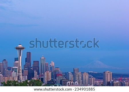 Seattle city skyline after sunset. Seattle city landmarks and Mt. Rainier at sunset.