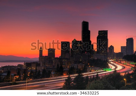 Seattle downtown glowing red in hot summer, freeway traffic in foreground - stock photo