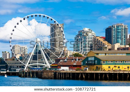 Seattle ferris wheel, waterfront and skyline on a bright sunny day with blue sky and clouds.  View is from the water.  Close up - stock photo