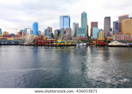 Seattle ferris wheel, waterfront and skyline on a bright sunny day with blue sky and clouds. View is from the water - stock photo