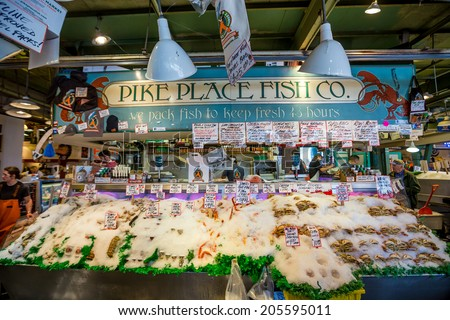 SEATTLE  JULY 5: Customers at Pike Place Fish Company wait to order fish at the famous seafood market on July 5, 2014. This market, opened in 1930, is known for their open air fish market style. - stock photo