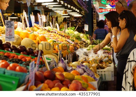 SEATTLE - JUN 3, 2016 - Young women buy fresh fruit at the Pike Place Market - stock photo