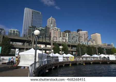 Seattle, 29 June 2014. Panoramic view of Seattle waterfront and downtown buildings on a bright day with sun and clouds.