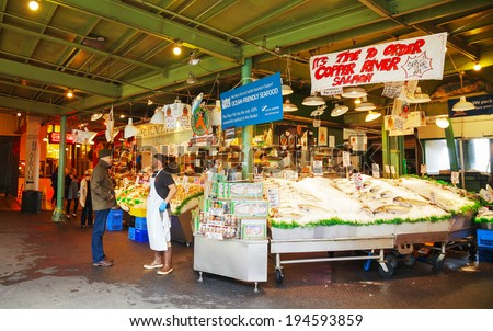 SEATTLE - MAY 9: Stand with tourists at famous Pike Place market on May 9, 2014 in Seattle, WA. The Market opened in 1907, and is one of the oldest public farmers' markets in the US. - stock photo