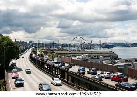 SEATTLE - MAY 10: Traffic on Alaskan Way moves past The Seattle Great Wheel Ferris wheel at Pier 57 near Seattle's downtown waterfront on May 10, 2014. - stock photo