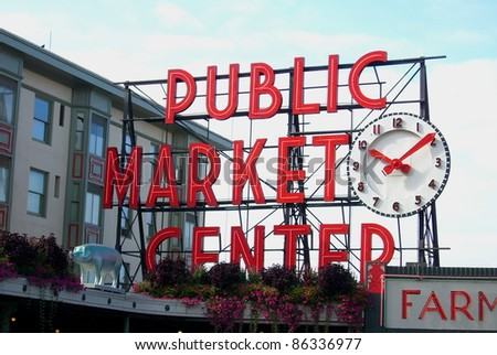 SEATTLE - SEPTEMBER 15: Clock and sign of the Pike Place Market on September 15, 2007 in Seattle, Washington. The market opened in 1907 and is still a major tourist attraction in Seattle. - stock photo