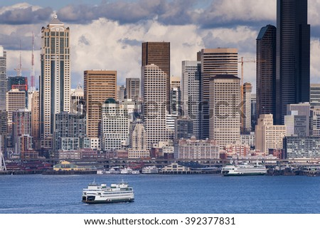 Seattle Skyline. A lovely spring day along the Seattle, Washington waterfront. This view across Elliott Bay pictures puffy clouds and ferryboats with modern office buildings in the background.