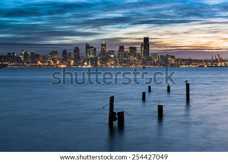 Seattle Sunrise. Sunrise over downtown Seattle with Elliott Bay and and old pilings in the foreground. Dramatic clouds add to the beauty of the landscape. - stock photo
