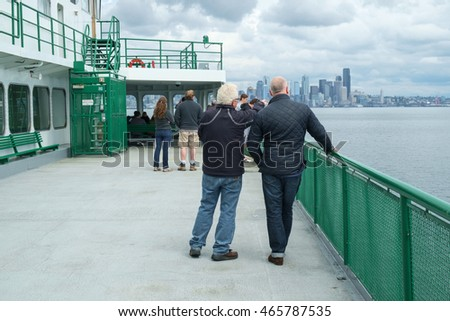 Seattle, USA August 7, 2016: Passengers on outside deck of ferry boat crossing Puget Sound approaching Seattle