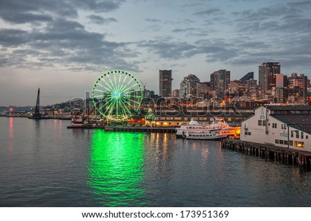 Seattle, USA, JANUARY 2014: Skyline of Seattle in the evening. A beautiful green lit ferry wheel is reflected on the water. January 18, 2014 - stock photo