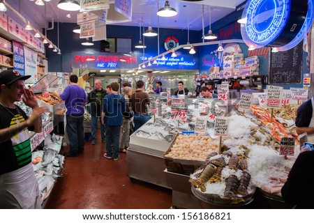 SEATTLE, USA - JULY 19: People buying fish  at Salmon stand at the famous Pike Place Public Farmers Market, on July 19, 2012 in Seattle, Washington,  USA. - stock photo