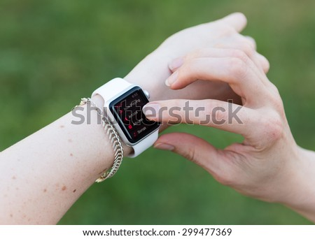 SEATTLE, USA - July 24, 2015: Woman Using Apple Watch While Outside. Using Music App to Play Songs.