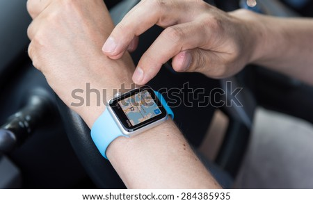 SEATTLE, USA - June 3, 2015: Man Using Maps App on Apple Watch While Driving Car - stock photo