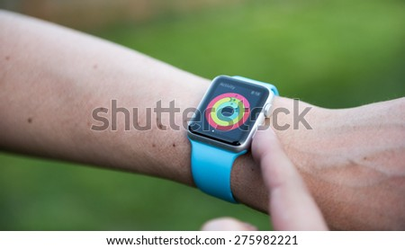 SEATTLE, USA - May 7, 2015: Man Checking Out Activity App on Apple Watch While Working Out Outside. - stock photo