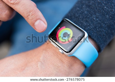 SEATTLE, USA - May 9, 2015: Man Checking Out Activity App on Apple Watch While Working Out Outside. - stock photo