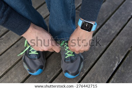 SEATTLE, USA - May 8, 2015: Man Tying His Sneakers While Wearing Apple Watch. - stock photo