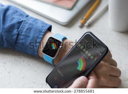 SEATTLE, USA - May 17, 2015: Man Using activity App on Apple Watch to See Calories Burned During Day. Comparing Watch and  iPhone Statistics. - stock photo