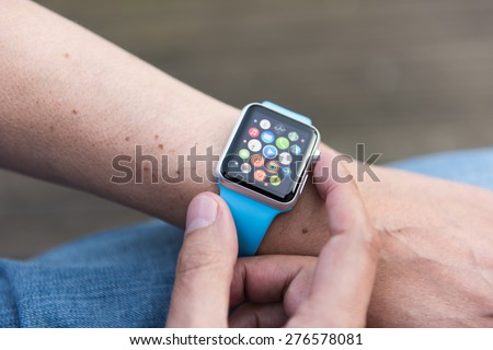 SEATTLE, USA - May 8, 2015: Man Using App on Apple Watch While Outside. Multiple Apps View. - stock photo