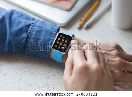 SEATTLE, USA - May 17, 2015: Man Wearing Sport Apple Watch with Blue Rubber Band. Emoji Collection Displayed. - stock photo
