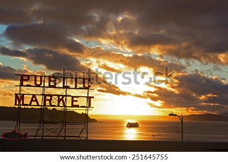 SEATTLE, USA - OCTOBER 26, 2014: A scenic sunset near the Pike Place Market on October 26, 2014  in Seattle, USA. Sunset over the water with a neon public market sign and cruise ship.  - stock photo