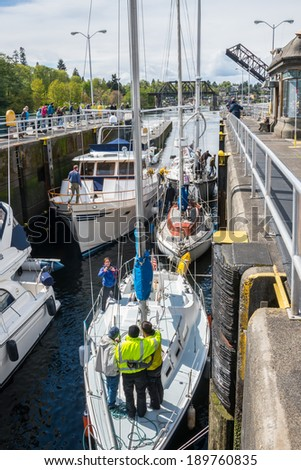 SEATTLE, WA - APR 27, 2014: Inbound Boats tied up in Hiram M. Chittenden Ballard Locks with spectators watching this popular tourist attraction in Seattle, Washington.  - stock photo