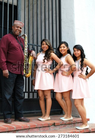 SEATTLE, WA__CIRCA MARCH 21, 2015__Muslim jazz musician and quinceanera teen girls posing together outside. circa March 2015 in Seattle, Wa. - stock photo