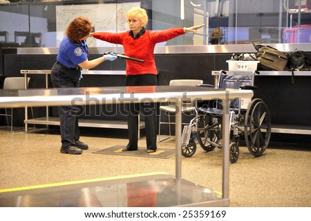 SEATTLE, WA-FEBRUARY 05:A TSA agent scans a passenger at Seattle-Tacoma International Airport (serving over 30 million people yearly) on February 05, 2009. The  poignant 9-11 message board is legible. - stock photo