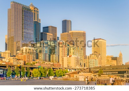 Seattle, WA. USA - July 7, 2014: Seattle Skyline at Sunset from the Waterfront. Visitors of the Waterfront can enjoy fresh seafood, shops, scenic ferry rides, or a visit to the Seattle Aquarium. - stock photo