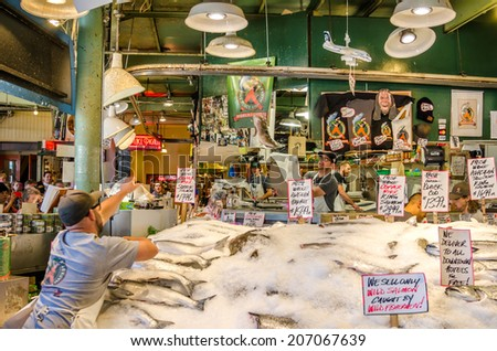 Seattle, WA, USA - July 8, 2014: The would famous crew of fishmongers throwing fish and having fun with custumers at Pike Place Fish Market. Founded in 1930, It is an historic open air fish market. - stock photo