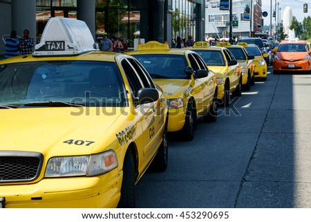 Seattle, WA, USA July 15, 2016: Yellow taxi cabs lined up waiting for riders. One orange taxi and line of several yellow taxis - stock photo