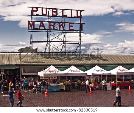 SEATTLE, WASHINGTON - JULY 13: Pike Place Market has served as the Seattle's harbor district commercial hub and farmer's/artist market since 1907.  Tourists mingle with locals on July 13, 2011. - stock photo