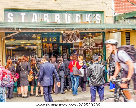 SEATTLE, WASHINGTON - March 15, 2015: Photo of the original Starbucks coffee shop. Starbucks recently came under controversy due to announcement that their baristas would discuss race with customers. - stock photo