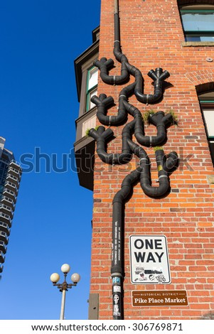Seattle, Washington, USA - March 1, 2015_drain pipes on a building wall in Pike Place Market area. - stock photo