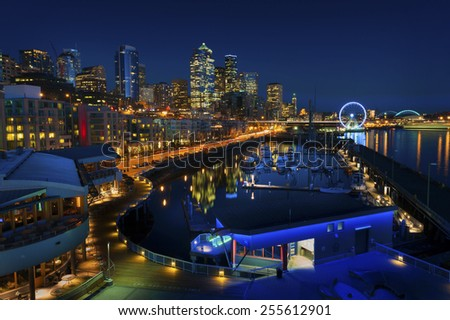 Seattle Waterfront at Sunset. The Seattle, Washington waterfront and skyline at sunset with a marina and ferris wheel. The Port of Seattle can be seen in the background. - stock photo