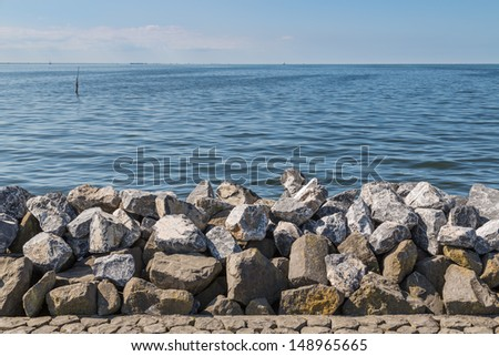 Seawall in the Netherlands made from big basalt rocks - stock photo