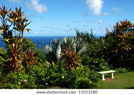 Secluded corner of paradise on Kauai, Hawaii.  Sitting bench is surrounded by tropical foliage. - stock photo