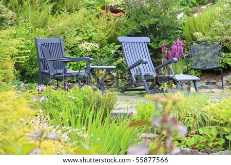 Secluded little patio surrounded by perennials. - stock photo