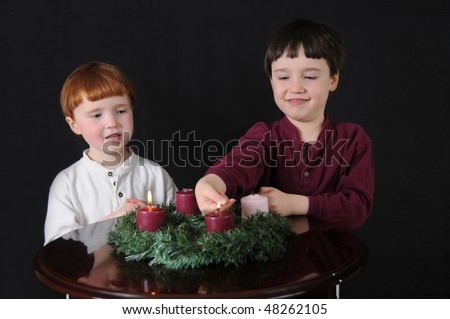 Second Week of Advent: Two brothers light an Advent wreath to prepare for Christmas - stock photo