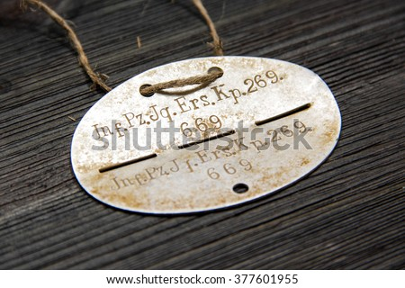 Second World War. Identification army badge of German soldier on a black wooden background - stock photo