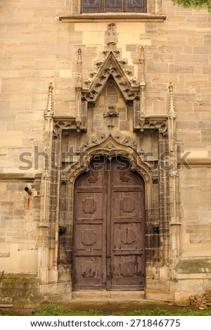 secondary entrance of old gothic church, detail on stone carved elements - stock photo