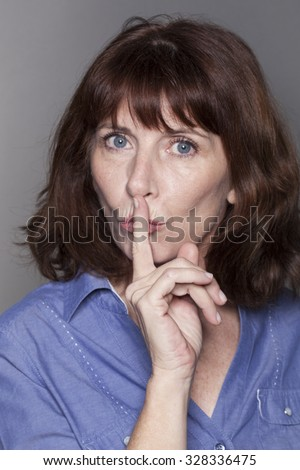 secret and taboo concept - teacher-like 50s woman wearing blue shirt asking for silence with finger on lips,studio shot