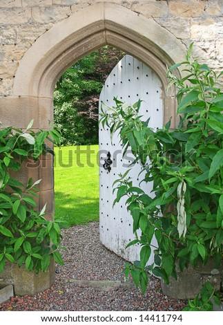 Secret Garden, sunlight lies beyond ancient garden wall and Arched Door - stock photo