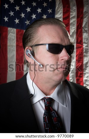 secret service man with american flag backdrop - stock photo