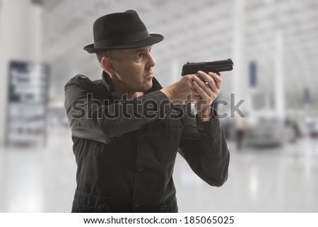 secret service man with gun on grey background - stock photo